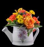Flores coloreadas vivas, rosas anaranjadas, en una regadera blanca, aislada Imagen de archivo
