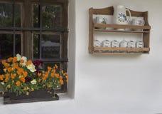 Flores coloridas em uma janela da casa da quinta Fotografia de Stock Royalty Free