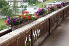 Flores coloridas en cajas en un balcón de madera en Austria Fotografía de archivo