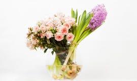 Flores coloridas en el florero de cristal contra el fondo blanco Fotos de archivo libres de regalías