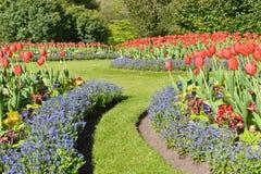 Flores coloridas y camino del césped en un jardín formal foto de archivo