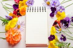 Flores coloridas y un cuaderno abierto en el fondo blanco Foto de archivo libre de regalías
