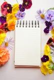 Flores coloridas y un cuaderno abierto en el fondo blanco Imagen de archivo libre de regalías