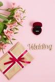 Flores com presente e anel em uma caixa no fundo cor-de-rosa Imagem tonificada, efeito do filme Imagens de Stock
