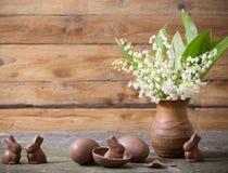 Flores, conejitos del chocolate y huevos Foto de archivo