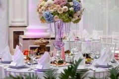Flores, copas de vino, servilletas y ensalada en la tabla Fotografía de archivo libre de regalías