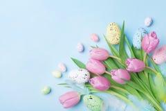 Flores cor-de-rosa da tulipa, penas e ovos coloridos na opinião de tampo da mesa azul Cartão feliz da Páscoa Fotos de Stock
