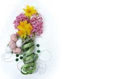 Flores cor-de-rosa e amarelas da mola, ovos coloridos, fita verde, do leste Fotos de Stock Royalty Free
