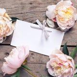Flores cor-de-rosa e Empty tag das peônias no fundo de madeira envelhecido Fotografia de Stock Royalty Free