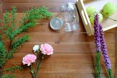 Flores cor-de-rosa e roxas doces com o frasco de vidro no fundo de madeira da tabela Fotografia de Stock Royalty Free