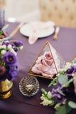 Flores cor-de-rosa e violetas nos florariums na tabela festiva violeta W Fotografia de Stock Royalty Free