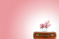 Flores cor-de-rosa no jarro na mala de viagem marrom velha do vintage Rosas no jarro Rosas cor-de-rosa Imagem de Stock Royalty Free