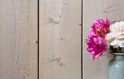 Flores cor-de-rosa no vaso cerâmico, decoração da mola com textura de madeira do fundo da parede Imagens de Stock