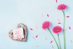 Flores, coração e caixa de presente cor-de-rosa do gerbera na opinião de tampo da mesa azul Cartão para o dia do aniversário, da  Imagem de Stock