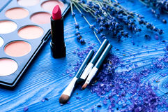 Flores cosméticas de la paleta y de la lavanda en fondo de madera Foto de archivo libre de regalías