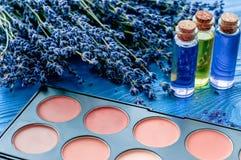 Flores cosméticas de la paleta y de la lavanda en fondo de madera Fotos de archivo libres de regalías