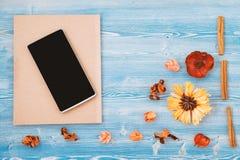 Flores, cuaderno y smartphone anaranjados y amarillos en un fondo de madera azul Textura y fondo Concepto para a imagen de archivo libre de regalías