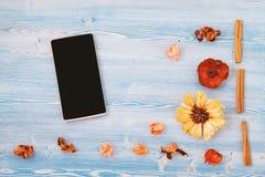 Flores, cuaderno y smartphone rojos y amarillos en un fondo de madera azul Textura y fondo Concepto para a imagen de archivo