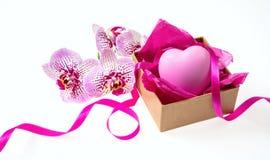 Flores da orquídea e presente pequeno com uma fita do cetim e um coração cor-de-rosa no fundo branco Fotos de Stock