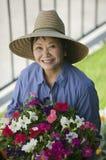 Flores da terra arrendada da mulher no jardim Foto de Stock