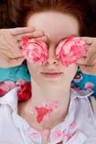Flores da terra arrendada da mulher nova na frente dos olhos Imagem de Stock Royalty Free