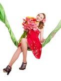 Flores da terra arrendada da mulher nova no balanço. imagens de stock royalty free