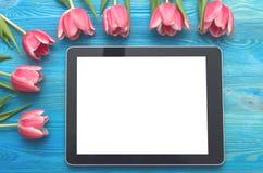 Flores da tulipa e dispositivo do tablet pc com a tela vazia no fundo de madeira com espaço da cópia conceito do dia da mulher Foto de Stock