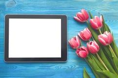 Flores da tulipa e dispositivo do tablet pc com a tela vazia no fundo de madeira com espaço da cópia conceito do dia da mulher Fotografia de Stock
