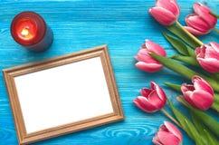 Flores da tulipa e quadro vazio da foto no fundo de madeira com espaço da cópia conceito do dia da mulher fundo romântico Fotografia de Stock