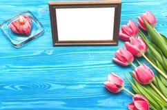 Flores da tulipa e quadro vazio da foto no fundo de madeira com espaço da cópia conceito do dia da mulher fundo romântico Fotografia de Stock Royalty Free