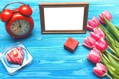 Flores da tulipa e quadro vazio da foto no fundo de madeira com espaço da cópia conceito do dia da mulher fundo romântico Imagem de Stock