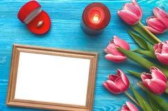 Flores da tulipa e quadro vazio da foto no fundo de madeira com espaço da cópia conceito do dia da mulher fundo romântico Imagens de Stock