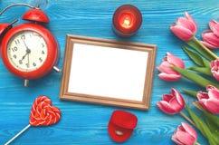 Flores da tulipa e quadro vazio da foto no fundo de madeira com espaço da cópia conceito do dia da mulher fundo romântico Foto de Stock