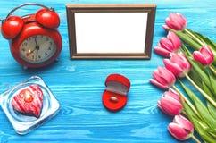 Flores da tulipa e quadro vazio da foto no fundo de madeira com espaço da cópia conceito do dia da mulher fundo romântico Foto de Stock Royalty Free