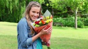 Flores de cheiro da jovem mulher feliz video estoque