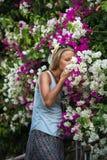 Flores de cheiro do turista louro novo da mulher no centro de cidade velho de Alanya Imagens de Stock Royalty Free