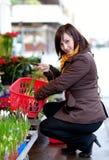 Flores de compra de la chica joven hermosa Fotos de archivo