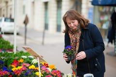 Flores de compra de la mujer en un mercado parisiense de la flor Foto de archivo libre de regalías