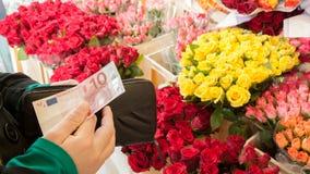 Flores de compra de una mujer Imágenes de archivo libres de regalías