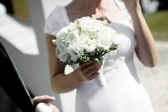 Flores de la boda en el primer de las manos de la novia Foto de archivo libre de regalías