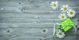 Flores de la caja y de la margarita de regalo en tablones de madera viejos Foto de archivo libre de regalías