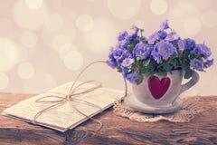 Flores de la campánula en una taza fotos de archivo libres de regalías