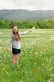 Flores de la cosecha de la muchacha del niño en el prado Fotos de archivo