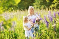 Flores de la cosecha de la muchacha y de la madre del niño Foto de archivo