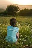 Flores de la explotación agrícola de la muchacha en campo en la puesta del sol Fotografía de archivo libre de regalías
