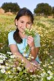 Flores de la explotación agrícola de la muchacha en campo en la puesta del sol Imagenes de archivo