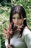 Flores de la explotación agrícola de la mujer en campo Imagen de archivo libre de regalías