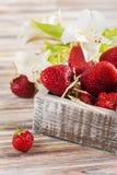 Flores de la fresa madura y del lirio blanco Fotos de archivo