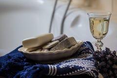 Flores de la lavanda, toalla, accesorios del cuarto de baño y un vidrio de vino blanco - balneario casero Foto de archivo libre de regalías