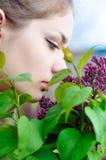 Flores de la lila de la muchacha que huelen adolescente Fotografía de archivo libre de regalías